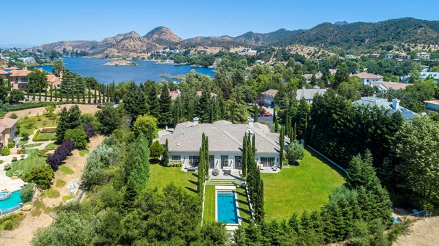 Located within the guard gates of Lake Sherwood & set amidst soaring trees, this sophisticated residence affords an impressive level of privacy on 1.22 flat acres. A winding drive creates a dramatic arrival to this spacious, single story home. The interiors blend seamlessly with the chic, clean-lined open floor plan, perfect for modern living on a grand scale. The two front rooms, an impressive dining room & handsome library, are adjoined by a romantic shared front patio that enjoys views of the entryway garden & water fountain. The vast great room is light & airy, boasting floor-to-ceiling windows & doors that lead outside. Dine al fresco on the extensive patio overlooking the pool & English Garden, featuring pristine white roses on a verdant canvas. The expansive, park-like grounds can also be accessed through the luxurious master bedroom suite. Additional membership to Sherwood Country Club provides amenities such as fine dining, golf, tennis, pool, spa & gym facilities.
