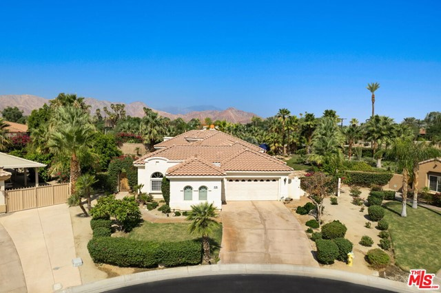 Welcome to La Quinta's secret gem at the beautiful Mountain View Country Club! Set on approximately a half acre of land, this unique home sits at the far end of a private cul-de-sac. Upon entering the courtyard, you will be welcomed by a grand rotunda foyer which sits beneath a striking custom chandelier. You'll notice the impressive 12 foot ceilings as the foyer opens up to the great room, dining room, kitchen and family room. The luxurious great room features a wet bar, fireplace, media center, and an extra room which can be used as a multi-purpose area. The gourmet kitchen boasts granite countertops, maple cabinets, built-in refrigerator, and convection oven. The recently updated travertine flooring throughout the entire residence will lead you through two master bedrooms. The first which features a huge walk-in closet, roman tub, shower, and direct access to the expansive backyard. Out back you will be wowed by one of the largest private outdoor areas in the entire community! A breathtaking meandering pool and elevated spa with waterfall is surrounded on either side by two expansive yards, leaving enough open space to make it your own. Use your imagination! The rear covered patio leads to a large fire pit area, great for entertaining among the numerous palm trees while stargazing on those lovely dessert evenings. You will also notice the large courtyard casita, which offers a great alternative for family and guests to escape to their own private and relaxing location. Nestled in one of La Quinta's most desirable gated communities, with a plethora of exciting and unique amenities, it is needless to say that this home is certainly one of a kind! Come take a look for yourself!