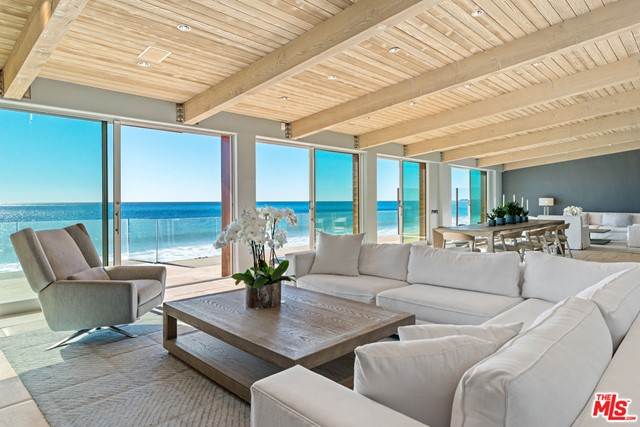 Gracious and stylish contemporary with 60' of beach frontage and non-stop coastline, ocean, and island views. High, wood-plank ceilings, skylights, stone tile floors, expansive glass doors facing the ocean for an atmosphere of luminous tranquility. Oceanfront living/dining great room with fireplace, built-ins, wet bar seating area, multiple glass doors onto a full-width deck for dining and relaxation. Sensational gourmet kitchen with island seating, granite countertops, quality appliances, beautiful wood cabinets. Three en-suite bedrooms on main level. Upstairs is magnificent owners retreat, expansive and tranquil, with spacious sitting area, generous built-ins and closet space, lavish bath, and large covered balcony. Gated front courtyard offers additional gathering space and barbecue island. Detached garage, guest parking, smart home technology. A stunning contemporary residence in an ultra-desirable location, with easy access to restaurants, shops, and downtown Malibu.