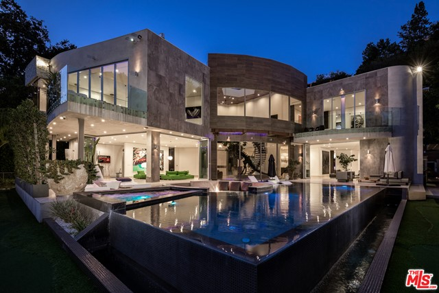 Modern architectural masterpiece in prime lower Bel Air. Nestled behind gates in a lush canyon setting, this exquisite contemporary is an entertainer's paradise w/over 10,000 SF of meticulously crafted living space. Enter the dramatic atrium complete w/curved staircase & soaring ceilings & experience an open-concept floor plan w/seamless integration of the indoors & outdoors. Highlights include a beautifully appointed chef's kitchen w/state of the art Miele appliances & LED lit kitchen countertop made of handblown Canadian glass. The master bedroom rivals the finest hotels, w/walls of glass & sumptuous spa-like bthrm. Entertain w/the 10-seat movie theater, billiard table, 200 bottle wine cellar, a exercise/steam rm. Outside, the grounds feature a cutting edge infinity pool, a water feature w/computerized rain bar & a sunken seating area w/fire-pit. Private & gated motor ct accommodates a dozen cars, w/3 car garage w/Tesla full house Battery back-up solar panels & additional guest house.
