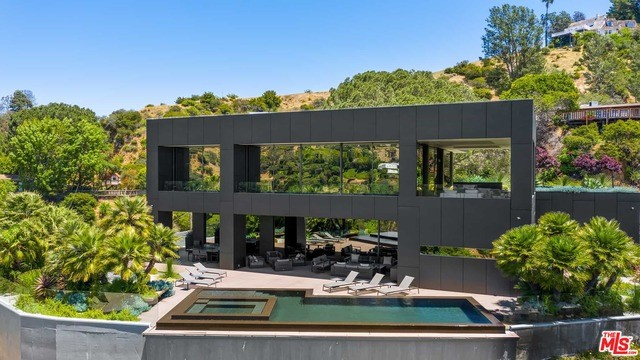 Ultramodern Steel & Glass residence atop private ridge in Coldwater Canyon. Ultimate Swiss technology provides an installation of architecture and beautiful contemporary design, fashioned for comfort, security, luxury & enjoyment. Entire walls of glass open to feature panoramic views of canyon, City & Ocean extending to Catalina Island on beautiful days. A towering Stone Pine signals the guest entrance from walled Courtyard to front door. Nature surrounds the setting and embraces the stunning architecture it protects. Nearly maintenance-free external fiber cement wall panels never require paint/maintenance. Triple-paned pneumatic windows & doors maintain constant perfect indoor temperatures on the warmest or coolest of days. Gallery walls showcase a world collection in every room. Blissful outdoor entertaining offers 2000SF of covered terrace, heated outdoor Kitchen & Dining, fire pit lounges--all overlooking serene views. A world class trophy.