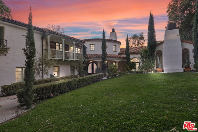 This Spanish Revival estate, known as Casa de Seis Palmas, has a storied Hollywood past and offers utmost seclusion and privacy behind lush landscaping. This luxurious celebrity hideaway has been home to actress Marion Davis, record mogul Ahmet Ertegun, and supermodel Tyra Banks. The home boasts an abundance of light and beautiful details like travertine stone and wood-planked floors throughout. The spacious living room is framed by a majestic vaulted wood-beamed ceiling, French doors, and grand floor-to-ceiling windows. A chef's kitchen comes replete with custom cabinetry, large center island, and top-of-the-line stainless steel appliances. The grand owner's suite features a sitting room, enchanting city views, and walk-in closets with gorgeous Spanish tile. An entertainer's paradise, the patio opens to a full outdoor kitchen, casita, fire pit, and pool. A library, sunroom, formal dining room, guest suite/media room with private entrance and full bath complete this one-of-a-kind home.
