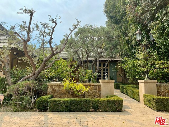 """Prime Little Holmby location - Located on a gentle, serene street, this one-story, three bedroom, 4.5 bath plus office in 4,115 SF home is located on 13,060 SF of flat land.  A pristine jewel designed by renowned architect, Bob Ray Offenhauser with a Montecito, sophisticated French Country influence, its architectural expression is unique and elegant. The home was custom built for the Seller in 2003 with authentic, high quality finishes and high attention to detail. The property is a gated, private oasis with sumptuous gardens surround by mature trees.  There are three en-suite bedrooms plus a den and office with additional 1.5 bathrooms; the office could be transformed into a fourth bedroom.  Upon entering the grand, recessed stone surround which frames the front door in Santa Barbara stone you will arrive through the impressive 12' foyer to the open floorplan, a superb entertaining flow leading from the entry to the dining room, living room and den.  These rooms feature 6"""" wide hand distressed walnut floors.  The formal dining room with an impressive vaulted wood beam ceiling is ideal for intimate or large parties and opens onto the gardens.  The expansive living room is dramatically accented by a vaulted wood beam ceiling and fireplace.  surrounded by 4 sets of French doors leading to the gardens.  The den/library with fireplace is finished with knotty alder wood paneling.  All rooms feature French doors leading to the gardens.  All three en-suite bedrooms have French doors which open onto beautifully landscaped gardens.  The sun filled master bedroom is complete with a grand walk-in closet and elegant bath.  The powder room has an artistic aesthetic with hand painted walls and ceiling.  Gourmet kitchen with granite counters, an abundance of alder cabinets, spacious walk-in pantry and a breakfast area looking onto the lush garden.  There is a spacious office with custom built-in cabinetry. The home has a generous amount of storage throughout including additional """
