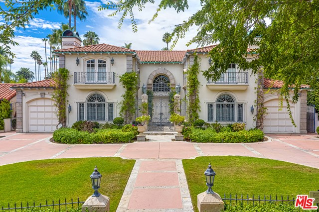Beautiful European-style Beverly Hills villa on one of the most coveted streets in The Flats. Architecturally balanced home was designed for entertaining. Ideal for owner- user wanting to make it their own. Enter the foyer with soaring ceilings, herringbone wood floors, and views of the yard. Left of entry is maids quarters, laundry, access to South garage, elevator to 2nd floor, and kitchen with butlers pantry and breakfast nook. Formal dining, family room with wet bar, and living room each access the veranda. The North wing is the study, 2nd garage, and Master retreat with sitting room, built-ins, walk-in closets, his and hers master baths with marble flooring. Upstairs offers open loft study, and jack-and-jill bedrooms on each side. The backyard has lawn, large heated pool, splendid veranda, pool house with 2 full baths, changing room, and 3rd garage. Quiet, yet convenient to world class shopping.