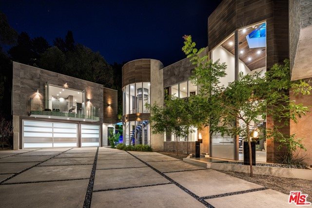 Modern architectural masterpiece in prime lower Bel Air. Nestled behind gates in a lush canyon setting, this exquisite contemporary is an entertainer's paradise w/over 10,000 SF of meticulously crafted living space. Enter the dramatic atrium complete w/curved staircase & soaring ceilings & experience an open-concept floor plan w/seamless integration of the indoors & outdoors. Highlights include a beautifully appointed chef's kitchen w/state of the art Miele appliances & LED lit kitchen countertop made of handblown Canadian glass. The master bedroom rivals the finest hotels, w/walls of glass & sumptuous spa-like bthrm. Entertain w/the 10-seat movie theater, billiard table, 200 bottle wine cellar, a exercise/steam rm. Outside, the grounds feature a cutting edge infinity pool, a water feature w/computerized rain bar & a sunken seating area w/fire-pit. Private & gated motor ct accommodates a dozen cars, w/3 car garage w/Tesla full house Battery back-up solar panels & additional guest house