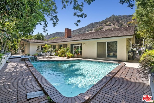 Opportunity knocks! Attention developers and owner/users looking for a major remodel project or rebuild on prime 14,000+sf lot in BHPO. First time on the market in 49 years, this 3 bed/3 bath+office 2,500+sf single level Mid-Century Ranch has open floor plan, center double-sided fireplace dividing living room and family room with beamed ceiling and 3 sliding doors to patio & pool/spa and private hillside. Dining room and den with vaulted ceiling off entry. Kitchen with granite countertops, stainless steel appliances, large pantry and breakfast room opening to side patio and backyard and a 3rd bathroom with access to the backyard and pool. Primary bedroom suite with 3 closets and sliding door opening to backyard and pool with Primary full bathroom with dual basins. 2 additional bedrooms, bathroom in hallway with dual basins and shower, and powder room off kitchen. Direct access garage. Bring your contractor and vision to create the next generation of this home in this beautiful BHPO neighborhood. Property sold AS IS condition.