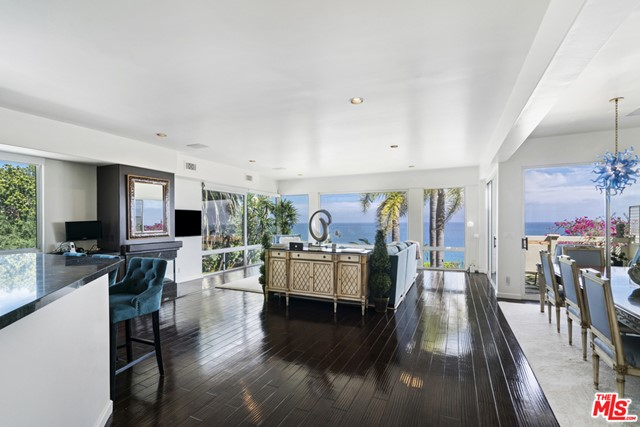 Rare opportunity to own the largest unit in this exclusive and storied boutique Richard Neutra beach bluff development more famously known as The Holiday House. Notorious for its classic Hollywood past where movie stars and the like would go to hideaway, this architectural gem still carries that same demand and luxurious privacy. With only ten units in total, this special corner unit has walls of glass on both floors giving you a panoramic view over gorgeous Escondido Beach and the Malibu coastline. On the first floor is the expansive living room, dining area and customized kitchen that all lead to your cozy ocean view deck. Upstairs are two more en-suite bedrooms with their own balconies. The master also has a large walk-in closet, romantic fireplace, wrap around ocean view balcony and an ocean view spa tub. This private and gated masterpiece also provides a large ocean view pool and sundeck, smart home control throughout, private walkway access to world famous Geoffreys restaurant and deeded direct access to Escondido beach which is one of the most beautiful and sandiest beaches in all of Malibu.