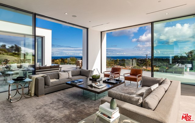 This gated contemporary estate in Upper Zumirez showcases sweeping ocean views and thoughtful, modern vision by the renowned Swiss Architect Roger Kurath Assoc.AIA/SIA of design21. The 8,200-sq-ft home boasts open, airy living spaces, surrounded by floor-to-ceiling glass walls and multiple terraces. Italian porcelain tile floors extend from indoors to out, while wood accents and cove lighting lend warmth to the interiors. The German Leicht kitchen showcases seamless modern design and Miele appliances. 5 bedroom suites include the stunning master with fireplace, soaking tub and Italian porcelain accent wall. On the lower level, find a second living room, wet bar, wine room, theater and fitness studio. The infinity lap pool, spa, rooftop terrace and expertly manicured, water-efficient grounds maximize the SoCal climate. Features include Control 4 tech, security system, 4-car garage, and dual driveways. Moments from Malibu's best beaches, shopping and dining.