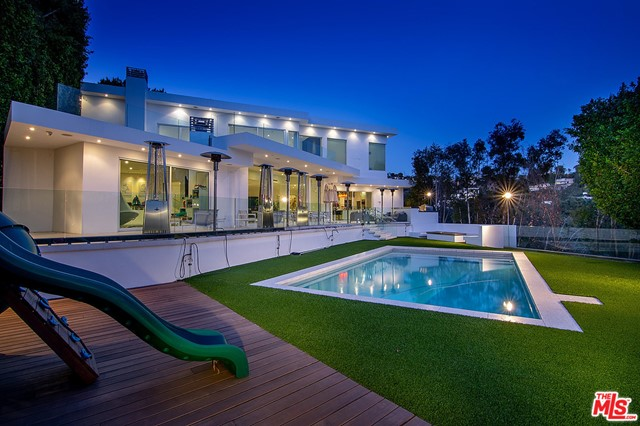 Sophisticated Modern estate in Beverly Hills with breathtaking City-to-Ocean views from every room.  Upon arrival thru a security perimeter, large stainless steel gates open to an expansive tree-lined motor court with parking for 12 cars. Enter thru automatic glass doors into a seamless open floorplan.  This back drops to motorized Fleetwood doors leading you to a grand back patio, salt water pool, fire pit, and heat lamps, perfect for entertaining. The home is bathed in natural light and with solar electric and pool heat. Upstairs is an incredible master suite with a fireplace and private balcony,  walk in closet and a spa-like bathroom. There, one can take in views to Catalina  & Long Beach.  A second BR suite completes the floor. This unique hillside property holds an abundance of mature fruit trees with walking paths amongst olive trees and mature oaks. Permits paid and plans submitted for mandatory approval for 1200 square foot ADU adding two bedrooms and additional 3-car garage if the buyer wants more. To make the transition easy, Seller will give a credit with BAM Luxury Audio Video Cinema to refresh the Crestron/Lutron system. Seller will also provide an allotment of pro basketball tickets on the wood for any full priced offer as an additional thank you. A street-to-street 1 acre lot nestled in a celebrity-studded area of one-of-a-kind homes.