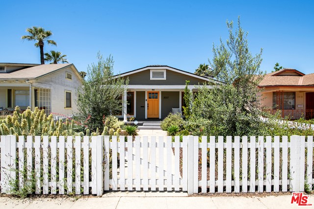 This stylish Craftsman has been thoughtfully restored by trendy Art Craft Homes. It exemplifies the perfect balance of bright & fresh contemporary feel with Historic preservation. The verdant front yard and wide porch are set behind an idyllic white picket fence. The open layout extends through the living room, which features an original fireplace, built ins, and molding galore, and past the dining area leading into the kitchen. A cook's dream, this inviting space boasts glass front cabinetry, wood top counters, farm sink and wood paneled dishwasher. Enjoy direct access to a spacious back yard with a double bay garage to use as you wish. Located on a charming block in the rapidly growing West Adams with lots of new surrounding development and more on the way.