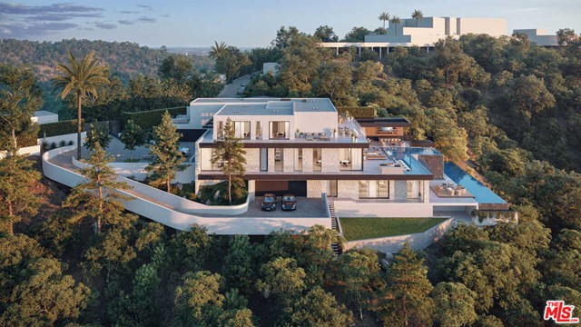 Situated on an ultra-private, tree-lined hillside in Bel Air, this spectacular, new estate captures far-reaching city and ocean views. Envisioned by Bowery Design Group with interior design by Faye Resnick, the estate boasts 1.3 acres, 7 beds, 14 baths, and endless amenities for indoor-outdoor entertaining. Showcasing soaring ceilings and exquisite detail, warm, modern interiors are positioned around a central courtyard. The chefs kitchen with pantry and living/dining areas open through glass walls to lounging terraces, outdoor kitchen, custom bar, infinity-edged pool, and Jacuzzi. On the lower level, find a lounge, bar, 12-seat theater, gym, steam/sauna, wine room, and 2nd 73 pool that extends over the hillside. 7 bedroom suites include staff quarters and a stunning primary suite with 2 closets. Features include an office, oak floors, and 2 garages with parking for 5. Capturing sunrise to sunset views, enjoy the utmost privacy, minutes from the citys best shopping and dining.