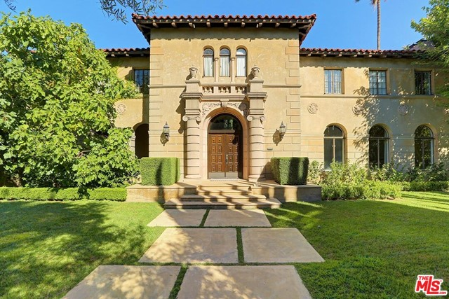 This spectacular 1928 Italian Palazzo is one of Hancock Park's very best! Hedged and gated for privacy and security, this stunning home offers old-world character and original period details that you simply don't find today. There is a dramatic 2-story entry with a double staircase and a beamed, stenciled ceiling. Palatial public rooms offer entertaining on a grand scale. Living room with impressive Deco fireplace surround and arched windows that lead to a library with built-ins opening to loggia, patio and yard. Exquisite formal dining room with classic wood-paneled walls. Spacious eat-in gourmet kitchen/family room that opens to an entertainer's patio. Butler's pantry, large-scale breakfast room/junior dining room overlooking rear patio/yard, and 1.5 baths complete the downstairs. Upstairs features a tremendous master suite, plus 4 generous-sized guest suites adorned with gorgeous 1920s tile. Detached one-bedroom guest house with living room and kitchen.