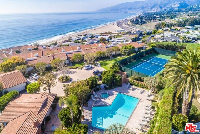 Stylish townhome on the bluff, perched above the Pacific, with white water views and coastline sunsets. Private pathway and stairs lead directly to the sands of Westward Beach and Zuma.  Exclusive 24-hour guarded, gated community, spacious living room with fireplace, bamboo floors, and adjoining balcony with spectacular ocean views. Carrara, jade marble and Italian ceramic tile floors throughout. Master suite is upstairs with enormous, walk-in closet and gracious master bath.  Second bedroom with alcove has view of patio and courtyard. Open kitchen with marble countertop, sea glass, and custom cabinetry. Downstairs is a large guest room and bath, plus access to the grounds. Attached 2-car private garage with additional guest parking steps away. Gated community has a beautiful, heated, saltwater pool and spa, tennis court, and lush landscaping for you to enjoy. Experience resort-style living, complete with dolphins, whale watching and healthy ocean breezes. Restaurants, schools & shops