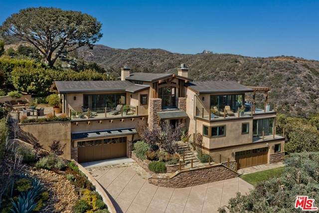 This private and gated panoramic view estate is unlike any other in the heart of the Palisades Village. The residence is set on an expansive promontory and features a stately stone facade, welcoming guests into the middle level. Via stairs or elevator, the top floor features a beautiful living room with fireplace that spills out towards the views and a recently redone island kitchen with top appliances. A formal dining room under elegant arches, family room, office, patio with firepit, and al fresco dining deck with BBQ and heaters finish the top level. Awe-inspiring views span from Will Rogers State Park to Downtown and Century City, to the jetliner views of planes landing at LAX below Palos Verdes, and the entire bay from Catalina to the edge of Malibu. The middle level features three ensuite bedrooms, including the master suite, with incredible views, a stunning bathroom with separate shower and tub, dual vanities, and a huge walk-in closet. The lower level is graced by a 700+ bottle wine cellar, tasting room, large laundry room, and a separate guest apartment outfitted with a living room, kitchen, bedroom, bathroom, and separate entry. The home is completed by two 2-car garages, walnut floors throughout, tankless water heaters, and a newer security/camera system. Completely rebuilt in 2006 by R&R Construction.