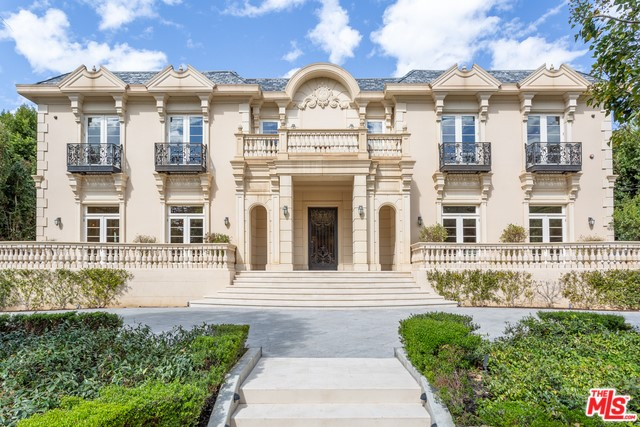 This grand traditional estate sits majestically on approximately 2/3 acre in highly desirable Brentwood Park. Beyond iron gates & a circular drive, rises the imposing faade of this mini-palace, complete with sweeping verandas, French doors and wrought iron finishes. The two-story formal entry hall is the center of this vast home - flanked by a sumptuous formal living room, grand dining room and impressive library. Well-appointed gourmet kitchen and an adjacent charming breakfast area overlooking the sweeping grounds. Custom salon bedecked w/ wood paneling & an exquisite vintage bar. 2nd flr master suite, w/ dual baths, private sitting area w/ fireplace, and a gorgeous outdoor terrace makes for an impressive peaceful retreat. Upstairs is finished with 4 add'l BRs all w/ private en suite baths, with a family rm perfectly situated among them. The lower level houses an expansive media room & maids' quarters. This is a home conceived to host and entertain at the highest level of luxury.