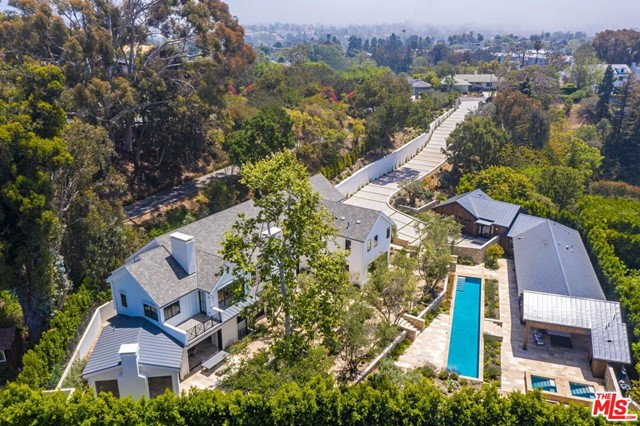 This brand new Backen-inspired contemporary farmhouse estate is a private green retreat set on a park-like acre in the Pacific Palisades, while only minutes to the beach. Behind reclaimed oak gates, a well-manicured driveway leads to the ultimate wellness & entertainment compound. Floor-to-ceiling doors throughout open onto outdoor entertaining areas featuring a 70 ft ozone lap pool, hot & cold plunges, bocce court and alfresco dining. Complete with a theater, gym, infrared sauna, & massive standalone barn guest house in the serenity of imported 50+ year old olive trees from Napa, blooming flowers, & edible gardens. This 8 bed, 11 bath beautiful home is crafted with world-class finishes such as French limestone, handmade tile, & European oak floors & beams throughout that fully harmonizes with its natural surroundings. Open, sun-kissed living spaces with high ceilings feature a living room with a double height fireplace and chefs kitchen. Upstairs house a multi-room primary suite boast