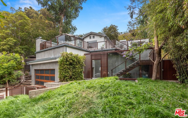 Contemporary, serene retreat in the highly coveted Santa Monica canyon. This sensational 2 bedroom, 3 bathroom home is surrounded by secluding landscaping with treetop views. The large grassy front yard features an added water feature that takes you out of Santa Monica and into your own personal resort. An oversized deck invites you into the home, featuring sitting areas for guests and a barbecue for unforgettable get togethers. You will be stunned by the contemporary details of this home abounding with natural light throughout. Entering into the kitchen, one is greeted with top of the line appliances including a Wolf oven, stove top and more. Greenery pokes throughout with large windows showcasing the trees and plants the property sits on. Earth is a central theme throughout the home, bringing prominence to the outside life beyond the property walls. Make yourself at home in this intimate, beautiful sanctuary minutes from the beach. The ideal and perfectly balanced Santa Monica lifestyle. Including a short walk to Canyon Charter elementary school.