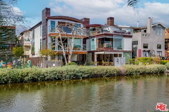 The Carroll Canal Compound located in one the most iconic residential communities. Two beautiful Architectural gems sit side by side with 60 feet of frontage on the historic Venice Canals. First time on the market these custom homes have adjoining lots with separate APNs. The properties offer many options for live/work, family/guests or just a magical artist compound. Both houses are 3 story structures with an abundance of natural light, elevators to all floors, 2 car garages and share the large back yard with built-in BBQ and Koi pond. The main house at 427 has floor-to-ceiling Fleetwood walls of glass on the upper and lower floors. The entry level is a gorgeous area with ultimate indoor/outdoor spaces. 2nd floor has two bedrooms, two bathrooms and a living room. The 3rd floor is a dedicated private master suite opening out to a rooftop deck with a wet bar, spa and fantastic views of the canals. The 2nd house, 425 is similar on its exterior, but the interiors are uniquely its own with 3 bedrooms and 2 baths. The main level includes a great living room with private deck, modern kitchen and a breakfast area. The top floor has 2 en-suite bedrooms, one of which has wood barreled ceilings with an extraordinary view. This is a setting that should not be missed. Close to beach, restaurants, shops and all things Venice
