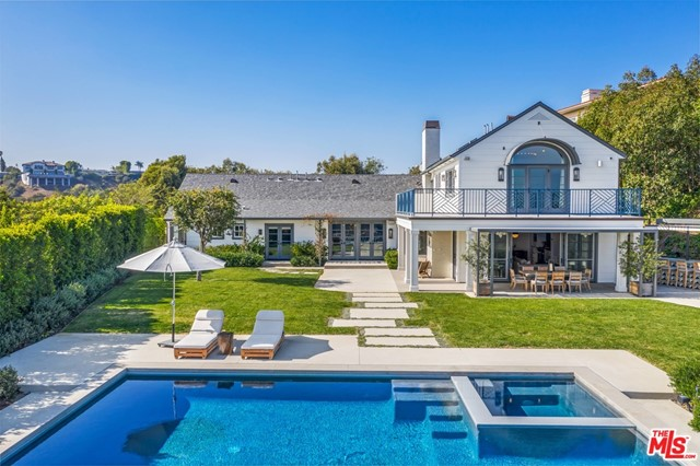 Privately secured behind a gated motor court entry and perched on 1.5+ acres atop one of Bel Air's most coveted streets, this serene haven offers sweeping views of downtown, ridge tops, canyons across to the Pacific Ocean. Completed in 2016, The Himes Miller Group reinterpreted this traditional Hampton-style residence with a progressive approach. The main level presents European hand-scraped white oak floors, a private study, formal sitting area, and 3 ensuite bedrooms. Top level primary quarters features wrap-around terrace with unobstructed mountaintop and ocean vistas, and a fully equipped gym and yoga studio for a focus on health, fitness and recovery. An open kitchen couples with the warm and cozy main entertainment room exhibiting reclaimed wood beams and indoor/outdoor fireplace. Abundant flat grassy land, outdoor bar, sunken fire pit, drop-edge pool and jacuzzi with ozone water system, horseshoe court, gardens & fruit trees. A Custom design to reflect comfortable luxury.