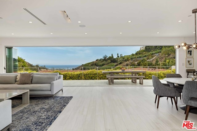 Gazing out towards unobstructed ocean views framed by mountains and vineyards, this single-level architectural residence was completely remodeled and expanded in 2017. Past a tranquil waterfall, guests are welcomed by an open floorplan into the main living space with a gorgeous living room, island kitchen with top appliances, and dining area, leading out via glass retracting doors to the breathtaking views. The outdoor spaces are a perfect combination of grass yard, entertaining patio, large spa, and sport court-all with ocean and hillside/vineyard views. The five bedrooms are well laid out, including the private primary bedroom with ocean views, multiple closets, and large bathroom with an oversized shower and dual vanity. The combination of gorgeous stone and wood design details with the abundance of natural light through massive skylights make this indoor/outdoor home a prime example of Southern California living.