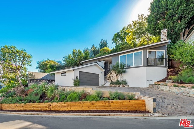 Meticulously remodeled Mid-Century in one of the most sought-after areas of Los Feliz. This home was restored with care to maintain the beauty and integrity of this iconic neighborhood all while offering the amenities of a new home. Vaulted ceilings and striking stucco fireplace greet you immediately as you enter the spacious living room. An expansive chefs kitchen features stainless steel appliances, quartz countertops, custom cabinetry, and an abundance of natural light. The kitchen opens to a dining room along with a patio perfect for alfresco dining. Downstairs features an inviting, oversized guest room with its own fireplace. Upstairs the master suite has a sliding glass door that leads to a private yard. Two additional bedrooms and guest suite are located on this level.  A beautiful, tiered yard offers privacy, stunning sunset views & your own herb garden, citrus trees & lovely drought tolerant landscaping. Some additional features include all new systems, hardwood floors & designer finishes. This home is perfect for families, entertainers & artists. Only moments from everything the city has to offer you will feel like you are living in your own private retreat.