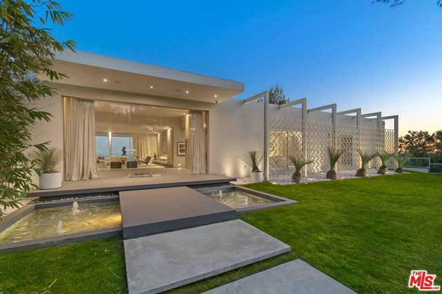 Perched upon the hillside of Trousdale Estates, enjoy one of the finest unobstructed 180 degree panoramic views in all of Beverly Hills. This vast tableau extends as far as the eye can see stretching from the skyline of downtown Los Angeles to Catalina Island. This can all be taken in from the infinity edge pool/jacuzzi as well as the master suite and most rooms in this open concept 5 bedroom modern villa. Welcome to Mid Century Modernism Redefined, a Steve Hermann design.  His top down 2 year renovation was designed to take full advantage of the view and to perfect the blending of indoor and outdoor space. Wonderfully illuminated throughout via multiple skylights and towering walls of glass yet elegantly designed with all the luxury and modern accoutrements worthy of this prestigious neighborhood within one of the most desirable zip codes in the nation.