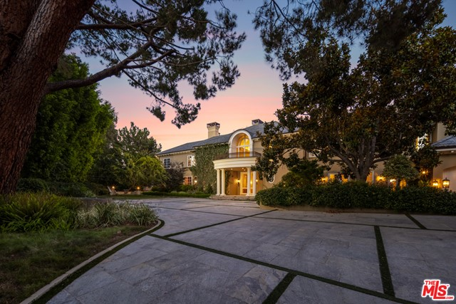 """Located in the prestigious, guard-gated, celebrity enclave of Beverly Park South, this 13,500 sq ft Georgian estate is sited on just over 2 enchanting acres with breathtaking city and canyon views. Selected and built by the developer as his own personal residence, and equipped with every modern and luxury amenity imaginable, this exceedingly secure & private estate is one of only a few Beverly Park properties affording sweeping city lights views. Luxury living spaces include state of the art gym with steam room and sauna, plush movie theater, wood-paneled library, and Master Bedroom wing with dual bathrooms and closets. Designer details include artisan crown molding, parquet wood flooring, and high-end, imported materials. The verdant grounds include rolling lawns, sparkling pool and spa, & several """"secret"""" gardens making this one of the most unique and desirable offerings in Beverly Park."""