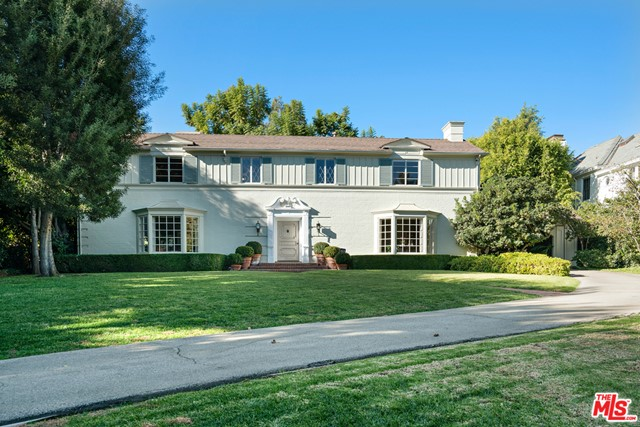 """Enchanting 1936 Neo-Georgian Revival manor in prime Brentwood Park on flat .71 acre, north of Sunset Boulevard on west side of prestigious Bristol Avenue. Five beds + 5 baths. First floor: foyer w/curving staircase, living room w/FP, dining room, paneled library w/FP; garden room w/FP & bar overlooking gorgeous rear gardens. Breakfast room, kitchen, butler's pantry, laundry room, maid's ensuite, back hall & powder room. Second floor: primary ensuite w/dressing, bath & sitting room. Three additional bedrooms + 2 full baths. California basement. Gated & fully landscaped grounds incorporate lush lawns, large swimmer's pool, brick terraces, mature fruit trees & 3-car garage reached via porte cochere. Extraordinary architectural detailing & design. Well-maintained for past 61 years by present owner. Build an elegant new home or move-in now as the estate is warm, welcoming & clearly puts the """"park"""" in desirable Brentwood Park!"""