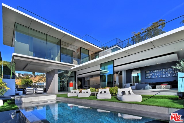 Perched high in Hollywood Hills West above the Sunset Strip, this striking 5540-sq-ft modern masterpiece is an ode to glass, space, and sightlines. Envisioned by renowned bicoastal architectural firm Fu Wilmers Design, 11-ft floor-to-ceiling vanishing doors, windows and glass- walled decks blur the barriers between inside and out, showcasing jetliner views that span from city to ocean to mountains across an infinity-edge pool. Each angle displays superior materials, from the full Miele kitchen to German Badeloft fixtures, within a flowing open layout and chic neutral palette. There are 4 spacious bedrooms, 7 baths, and a skylit lower-level flexible entertaining space with a bar, gym, wine room and a Dolby Atmos theater; its an integrated smart home as well. Built just in 2018, this extraordinary property is now fully realized in every aspect, from its impeccable landscaping to its newly finished wooden rooftop decks. Rise above it all and live above it all in this unforgettable oasis.