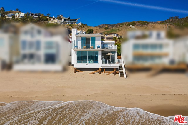With its stunning views, desirable location, and striking contemporary design, this La Costa beach house is the perfect setting for the Malibu lifestyle. Wraparound windows and decks on two levels invite sunrise-to-sunset appreciation of the ocean's ever-changing panorama. Just inside the gated entry is a serene and very private walled garden with room for yoga or a quiet writing table. Through the front door, it's all about the view as stone tile floors, recessed lighting, and floor-to-ceiling glass emphasize clean lines, an open layout, and great indoor-outdoor flow. The living room, with a fireplace, adjoins a spacious dining area. Both open onto an oceanfront deck for barbecues and al fresco dining. The ocean-view kitchen is equipped with top-grade appliances, granite countertops, lots of built-in storage. There's also an ocean-view den/office/media room, full bath, and laundry room on the main floor. Three bedrooms upstairs include a sensational ocean-view owners suite, with wood floors, fireplace, spa-style stone-tiled bath, and two oceanfront balconies with hot tub and room for lounging and stargazing. Stairs to the beach, outdoor shower, two-garage with work station, and built-in cabinets and storage. Air-conditioned for year-round comfort, this lovely contemporary La Costa residence is perfect for casual beach living and lively entertaining.