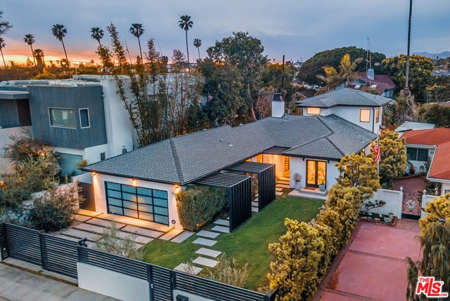 Stunning architectural Venice home boasts California indoor-outdoor modern living. The light-filled open floor plan shines as walls retract blurring the lines between its interior and exterior spaces. The yard features green grass, a gated perimeter, and modern architectural walkway leading you to the front door. Upon entry you are welcomed by warm, rich hues of the wide plank flooring that beautifully balance industrial finishes, built-in speakers, and smart home technology. The chic chefs kitchen is great for entertaining as it opens to the spacious dining area and living room anchored by the large fireplace and wall of windows extending the living space outdoors. Smartly designed, this floor plan includes a primary suite downstairs as well as a primary suite upstairs, a choice rarely given to homeowners. The main floor is rounded out by two large bedrooms (currently used as an office and a gym), and a gorgeous full bath. The primary suite on the second floor includes an enormous custom walk-in closet with a dressing area. Well-thought out landscaping and exterior spaces offer areas to relax and play. Attached 2-car garage directly off the service area makes coming in and out a breeze. Spectacular lifestyle location near shops, restaurants, Abbot Kinney, Venice Beach and the whole cultural scene. This undoubtedly is the house you'll want to call home!