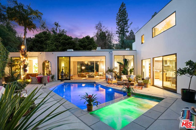 Holmby Hills hidden oasis. Nestled behind bamboo hedges and secluded from the street, this radiant architectural home feels far from the bustle of city life yet is moments from the Beverly Hills Hotel and Rodeo Drive. Built-in 1961 and stunningly reimagined in 2017, the gated residence showcases a classic midcentury aesthetic infused with timeless contemporary flourishes. Warm, sophisticated living spaces, including a soaring great room with fireplace, den with bar and chefs kitchen lined with Fleetwood glass doors, fostering a harmonious connection to a private backyard with a pool and spa immersed in an understated jungle canopy. The primary suite opens to a private patio and pool beyond and features a staggering showroom closet and magnificent bathroom overlooking a serene meditation garden. Both private and secure while located in one of L.A.s most prestigious neighborhoods, this home feels like an exotic retreat yet captures the quintessential spirit of Southern California.