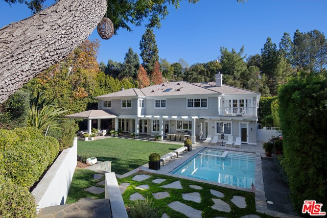"""Extraordinary 2- sty Trad Estate tucked away on a pvt st off lower Mandeville Cyn. Set behind a tall gate and hedges on over 1/2 acre of land w/ grt privacy, seclusion & quiet. 2 sty entry leads to well-detailed formal living/dining rms & inviting lib/bar rm. Fab """"great room"""" encompassing cook's kit, breakfast area & lg fam rm w/ FP opens thru numerous French drs to 2 covered outdr living rms, expansive, lush pvt yd w/ lawn, patios, bbq, pool/spa, terraced garden, walking paths & children's play hse. Lg gym/playrm or 6th BD, butler's pantry, laundry rm w/ dbl machines & direct access 3-car gar complete the 1st flr. 5 spacious BDs upstairs, each w/ vaulted clgs, en-suite BA & walk-in closet. Exceptional master suite with sitting rm + off/gym, FP, terrace, grand scale BA & dual fitted closets. Lg 2nd fam rm completes the 2nd flr. A true ctry retreat w/ the feeling of being out of LA, yet in close proximity to all that BW has to offer. A special offering for the most discriminating buyer."""
