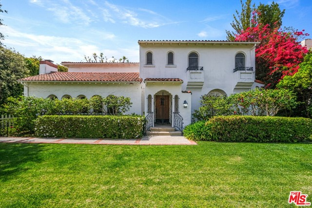 Rare opportunity in the prestigious Beverly Hills flats. This 12,105 SF lot includes a 4154 SF quintessential Mediterranean-style main house with 6 bedrooms and 4.5 baths, plus a coveted, permitted 1300 SF 2-story guest house with full kitchen and large rec room. The elegant main house features timeless arch and pillar designs, vaulted ceilings in living room and den, spacious windows for natural sunlight, sliding glass doors for indoor/outdoor living, formal dining room overlooking pool and garden, well-equipped kitchen with breakfast nook, home office with built-ins and generous bedrooms. The secluded backyard provides a tranquil and private setting for al fresco living with lush landscaping, bright florals, soaring trees and a dazzling pool. This classic main home plus full guest house compound is located on a serene, tree-lined street, far from traffic, a 5 minute walk to El Rodeo Elementary School and a few blocks from Rodeo Drive shops and Beverly Hills restaurants and entertainment. A gem in a world-class locale, the possibilities are limited only by imagination.
