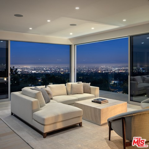Nestled quietly atop a Japanese Garden, minutes from the Sunset Strip, The Residence at Beverly Grove offers respite within nature. As you approach you are welcomed by the ease of a slow moving gate. The front door opens & you are greeted with a flood of sunlight from the large skylight above. White oak floors & reclaimed walnut panels compliment the natural surroundings. With large glass panels that slide open to extend the indoors out & the outdoors in, decks to gaze upon the gardens & 180 degree views of LA, the residence becomes as much a part of the garden as it is a jewel within the landscape. White in contrast to the bamboo trees below, the natural beauty of the home blends seamlessly while still maintaining an identity all its own. The residence feels light as it rises above the shimmering light blue water of the pool below. This home is a true masterpiece that must be viewed to be truly appreciated.