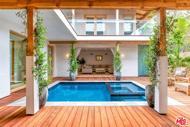 Situated just steps from Abbot Kinney and a short stroll to Lincoln and the beach is this Balinese-style Oasis. Gated, hedged, and completely private, this Venice compound features 5BR/4.5BA, with sleek, open & airy interiors designed for maximum indoor/outdoor Southern California living. The home's indoor/outdoor areas include a state-of-the art kitchen, spacious family/media room, and living room with floor-to-ceiling glass Fleetwood pocket doors that flow out to the covered veranda. The tropically inspired residence also features a central courtyard, complete with pool & spa, as well as 2000 SF of lanai decking  which nearly doubles your usable outdoor living space. Floating above the pool area is the impressive master suite with fireplace, large walk-in closet, and beautiful stone bath, all opening onto the wrap-around upper level lanai. The property is gated and surrounded by a perimeter of mature Kentia Palms and lush Ficus hedging. Additional features include brand new imported white oak floors, natural stone slab baths, laundry room, gated entry, two-car garage + two-car off-street parking, plus gated alley access. Close to all of the best Westside restaurants and shopping, this truly is the best house in Venice.
