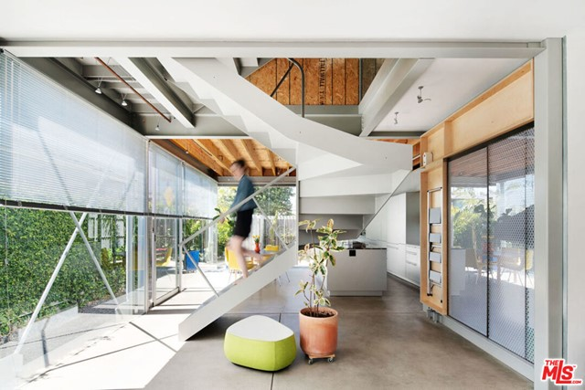 """Winner of the AIA 2020 Merit Award for Residential Architecture, The """"Y"""" House is a stunning live/work residence designed by Cigolle X Coleman Architects for themselves. Featuring 2 bedrooms, a studio & 2 1/2 baths, the house is tucked behind Abbot Kinney, just blocks from the beach. The spiraling switchback steel staircase at the center of the house organizes the living spaces. The contrast of materials - from stainless steel & perforated anodized aluminum, to raw plywood and hand-plastered surfaces - blend refined cutting-edge details with an artistic Venice aesthetic. The open plan ground floor looks out to the garden and patio through walls of glass and contains living, dining and kitchen - outfitted w/ Bulthaup cabinetry, Miele appliances & Marmoreal countertops. The private master suite encompasses the entire middle level and offers custom cabinetry, Poliform closets, a stand alone tub and walk in shower. On the 3rd floor you'll find a second bedroom with en suite bath, along with a large studio/playroom with its own kitchenette - a very adaptable space flooded with natural light. The house boasts radiant heated concrete & hardwood floors throughout, Fleetwood doors & windows as well as a customizable Lutron lighting system. The rooftop deck offers dramatic views of the city and Santa Monica Mountains while still maintaining a feeling of privacy."""