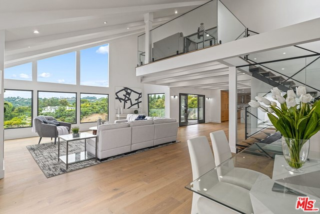 This newly renovated contemporary Beverly Hills estate astonishes w/ breathtaking mountain vistas, soaring ceilings, and light wood & marble finishes throughout rounding off this prestigious home.  A grand entry establishes the luxurious aesthetic w/  modern open floor plan, allowing for a seamless flow through the living, dining, and kitchen areas. Beautiful soaring windows, & sliding glass doors throughout give it its bright & serene indoor/outdoor feel. Cook w/ poise in the sleek chefs kitchen w/ marble accents and elegant center island, grand farmhouse style sink, and top-of-the line appliances. Unwind in the master suite boasting a vaulted ceiling, & private balcony overlooking the lush views. A polished feel throughout, the decadent bath features an expansive glass shower, tranquil soaker tub & dual vanity sink.  Amenities include spacious loft, extensive balconies, cozy fireplaces, well-appointed guest rooms & lavish baths! Soak up California living in this heavenly estate!