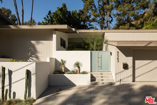 Entirely remodeled and expanded architectural gem is a Robert Skinner A.I.A mid century modern on a private street in BHPO. Behind a gated entrance; keeping in-line with the mid century period, stands a pivot door and ridged glass front wall leading to the inviting open floor plan for this 3 bed 4 bath home. The elegant decor brings attention to the restored nods of 1960s design such as the double sided original fireplace anchoring a gracious sunken living room and lounge area both walled in restored wood beams & panels, angled ceilings, & Terrazzo flooring. The bespoke craftsman built bar faces the open dining area and designer kitchen. The primary bed offers a stone fireplace, Amangiri style wet spa and custom cabinetry. The fenced and hedged backyard, reminiscent of a palm springs retreat, invites more than just private enjoyment with a full built in fire-pit, outdoor kitchen and grill and seating, all anchored around a reflecting pool/spa amongst the carefully crafted landscaping.