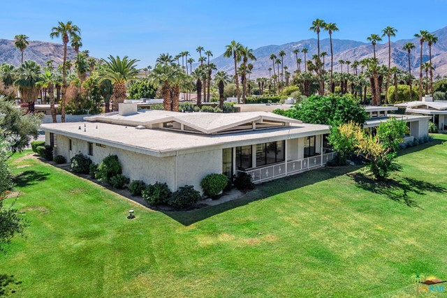 Rarely available Canyon Vista Estates townhome in South Palm Springs on Fee Simple (you own) land. Just one of 26 units on 8 acres of land this home has been in the same family for three generations. Built in 1976 in the Palmer & Krisel Mid Century style, this home features very spacious rooms as it encompasses just under 2700 sq. ft. on an elevated view lot. The large primary bedroom showcases mountain views looking to the West and North and also has two walk in closets, vanity dressing table complete with make up lighting before entry into the full bath with shower and soaking tub. The other very spacious guest room also has a private bath and walk in closet with enough room for a sitting area too. Large great room with clearstory windows is the centerpiece of the home with step down bar with sink and soaring ceiling heights showcasing the beautiful surroundings and outdoor living areas. Adjacent to the great room is the more intimate family/den with slump stone fireplace. Separate kitchen with dining area has been updated with newer cabinetry, counters, appliances and tile as well as the spacious adjacent powder room and laundry room. Newer tile flooring and carpet throughout with direct access from the two car garage. Canyon Vista Estates features two pools and spas and private tennis court. One look and you will see why this home has been the respite for the same family for generations.