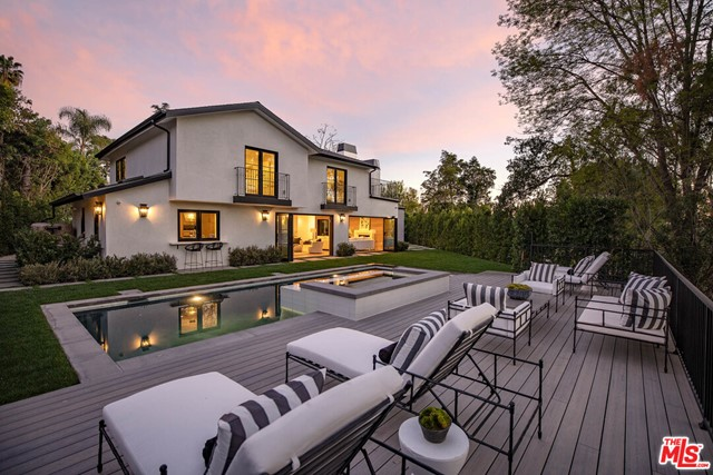 Luxury California living at its finest, come home to this newly re-imagined Beverly Hills estate. Sited in a world class locale, this stunning retreat is minutes to the best shops, restaurant & in Benedict Hills HOA w/community tennis courts & security patrol. Be mesmerized by the curb appeal as you are greeted by meticulous landscaping & soaring trees which lead you to the dramatic double height glass door entry. With a sweeping open floor plan, the home boasts endless entertaining opportunities & features a decadent bar, wine cellar, formal dining & multiple living spaces w/accordion glass doors for an indoor/outdoor flow. At the heart of the home is a voluminous formal living w/fireplace & floor-to-ceiling windows. Gourmet kitchen w/Wolf appliances, eat-in island, pocket windows to outdoor bar top, & walk-in pantry. A dramatic staircase brings you to the 2nd level with generous guest suites, laundry room, & private primary wing. Spacious master w/marble clad fireplace, lounge, French doors to the sweeping patio for morning coffee or evening drinks, and en suite bath w/dual vanity sink, glass shower, soaker tub and two well-appointed walk-in closets. Whether enjoying a dip in the pool or al fresco meal from the BBQ, the yard is suited for any event & is enveloped by greenery for the most serene environment. A true dream built w/no-expense spared!