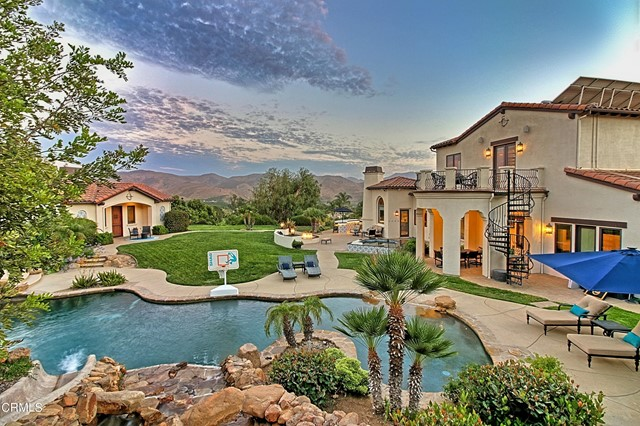 This unique 2 acre estate is nothing less than majestic. A Mediterranean (with a Spanish flair) masterpiece. Located in  a posh Camarillo neighborhood. 180 panoramic views. Thriving avocado orchard (but could be a lot split situation?).Master, along with 4 bedrooms  are on 1st floor. Mstr. has a fireplace, 2 walk-in closets, doors to the exterior  along with a remarkable bathroom. Beautifully  remodeled kitchen which opens up to the family room. The dining nook features a cozy fireplace and a mini fridge.  The HUGE exercise/game room has a wet bar, fridge and storage cabinets.  It located upstairs & has its own private balcony w/ a  stair case leading to the well manicured grounds with a sprinkling/drip system. There is a fully equipped  detached 1+1 guest home w/ a fireplace and its separate yard area. Beach entry free form pool with a waterfall  and slide. Two oversized finished 2-car garages. Ample  parking in the driveway as well. Outdoor living at its best with the astounding grounds, fireplace,spa,multiple sitting areas, lest I forget the amazing built in bbq (taking in the incredible views as you grill).  Just down the street is a great park.  Truly, I have not described this home as it deserves....... It is an astonishing, unique home.