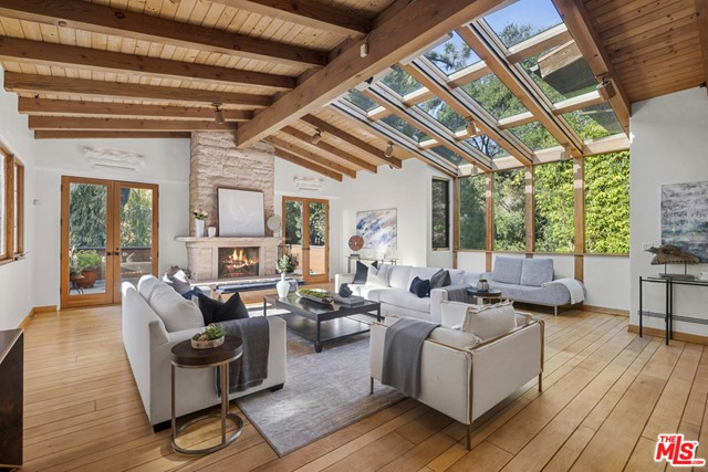 Serenity in the city. Sitting high above the street up a gated driveway on a quiet & beautiful tree lined street in the Estates section of Old Hutton, just minutes from the heart of the city.  This 5 bed + 5.5 bath celebrity retreat on almost half an acre boasts character & detail throughout. Soaring high vaulted beamed ceilings & huge custom skylights, large picture windows drench each spacious room w/natural light. Home gym, guest quarters & library. Upstairs, the spacious main suite w/elevated ceilings, 2 walk-in closets & tranquil bath w/Japanese teak soaking tub looking out to a large zen garden wall fountain. The outdoor grounds provide plentiful gardens w/a lush hillside orchard, large solar-heated pool, hot tub & deck, koi pond, grass pad & sports court. This one-of-a-kind property is a tucked away private oasis just moments from the heart of Beverly Hills & the great restaurants & shops at the Glen Centre, in coveted Warner Avenue Elementary.