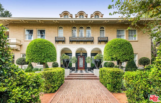 Originally designed by architectural icons Hunt & Burns in 1914, this stunningly restored, historic estate is a gateway back in time. Seamless blending period details and modern amenities, the interiors evoke the glamour and prestige of the roaring 20s and Great Gatsby. The 2-story entry showcases handcrafted details, wainscotting, tray ceilings, and elaborate moldings. Formal living and dining rooms flank the entry, while the chef's kitchen boasts custom finishes and marble countertops. 9 bedrooms include the elegant master suite, with separate spa-like baths, custom closets, and a private terrace. Journey downstairs to find a speakeasy, cigar lounge, home theater, and gym. Separate guest house, manicured grounds, herb gardens, alfresco dining terrace with caf lights, outdoor kitchen, pool, spa, and poolside cabana with fireplace round out the property. Offering absolute privacy among majestic gardens and mature trees, this Hancock Park estate is unlike anything else you've ever seen.