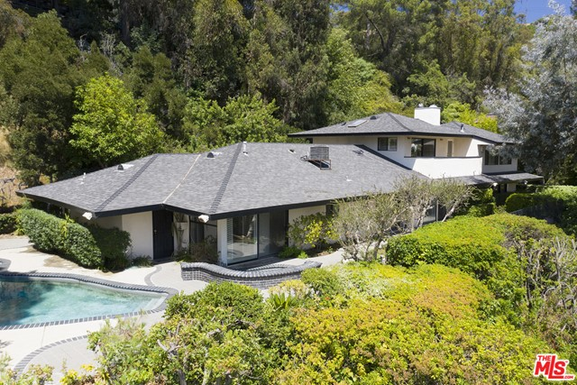 Now $1 MM under original LP! Rare sprawling residence, flush w/ Mid-Cent Lloyd Wright-esque influences; deep overhanging eaves, floor to ceiling glass, clean lines & utter privacy, in 24/7 guarded Hidden Valley Colony.  Recent sales at $17MM, yards away & other $30+MM valued homes, make this an ideal opportunity to expand/renovate/redevelop a large site w/gated drive or move in and get a toe hold as resident in the least expensive home to sell in the Colony in years.  Multiple A-list Celeb enclave w/discrete clientele.  1st flr: open concept liv/din flows to generous patios & pool w/cyn views, plus 2 bds & 2 bas. Upstairs, enormous 2 bd/2 ba ste, superb bed ste/in laws.  Topping it off:  2 blocks down this pvt rd is the residents only access gate to Franklin Canyon walking trails, lake & nature center, including vast seldom used open space.  A green, pastoral environment, like living in Topanga or Malibu countryside, yet 5 minutes to the BH Hotel & easy access to Sherm Oaks/Studio City