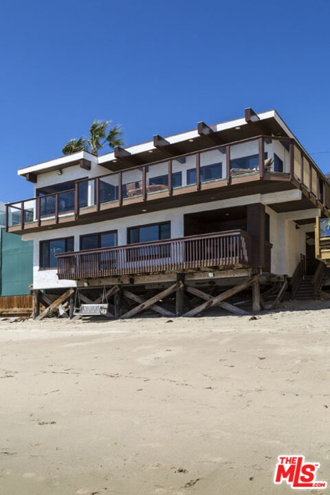 Great Malibu Road Beach home. The Dom Deluise Family Beach Home on the market for the first time in over 40 years. Gated entry leads you to a great entertaining seating and BBQ area. Entry level has very spacious open living, kitchen and dining area, all opening to an entertaining deck. There is also a powder room, and 2 bedrooms with full bath on this entry level. Lower level with oceanfront master suite, walk-in closet and bath with soaking tub, shower and sauna. 2 bonus rooms, great for office/gym/baby's room and additional full bath. Separate guest room/4th bedroom, walk-in closet and bath above garage with wet bar and deck. Easy beach access to a great sandy stretch of beach on Malibu Rd. Sale subject to existing Lease.