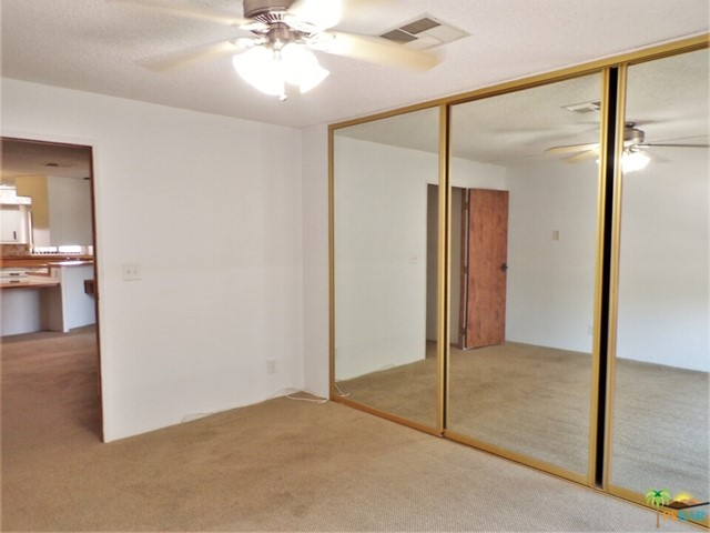 A Mirrored Door Closet Provides Storage Along One Wall In e Master Bedroom
