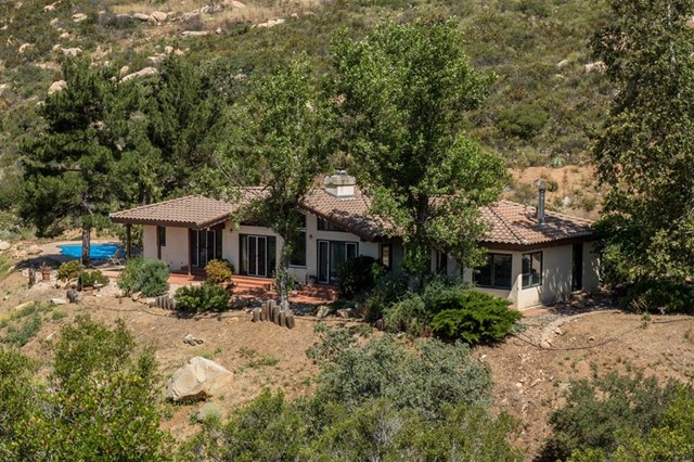 Beautiful home and guest house in Jamul on 12+ ac with peaceful views of lake and mountains.  Rare gem in quiet valley is only 40 min. to airport. 1-story main house, oakwood flrs, remodeled kitch, baths and interior, lots of light. 2nd story guest house w/250sf covered deck over 850sf 3-car garage enjoys stunning views of Lyons Peak; luxurious and cozy with heating/ac, kitchen, W/D, ++.  Solar pwr provides energy to both homes and new well. Jacuzzi and pool overlook oaks, valley and mountains beyond. Neighborhoods: Lyons Creek Valley Equipment: Pool/Spa/Equipment Other Fees: 0 Sewer:  Septic Installed Topography: LL,GSL,SSLP Guest House Est. SQFT: 588