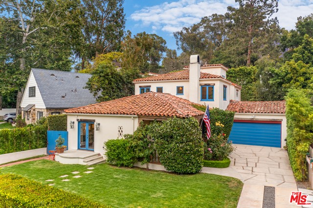 On desirable San Lorenzo Street, where the road widens and the neighborhood quiets, you'll find this quintessential Santa Monica Canyon home, exuding charm from each of the original 1927 Spanish details, while offering all of the modern necessities of today. Tall hedges create a large, private, grassy front yard, ideal for relaxing, picnicking, or playing catch. The front porch is masked by roses and peach trees, making a romantic entry. Enter the living room, fitted with a smooth stucco fireplace, tall windows, and wood ceiling. Each room naturally flows to the next, with the dining room opening to the front yard, breakfast nook, and then to the kitchen. The kitchen is the heart of the home - the use of bright colors and textures makes it both aesthetically pleasing and joy-producing. Downstairs also features two large bedrooms and the family room, which opens to the backyard. The yard is large enough for a pool and is ideal for family, games, and entertaining. Upstairs includes one secondary bedroom, plus the primary suite, which offers views of the blooming jacaranda trees, tons of natural light, and a separate space, perfect for an office or sitting room. Enjoy every inch of this unique home and fall in love with the neighborhood, moments from the beach, Canyon Charter Elementary school, shops, and restaurants.