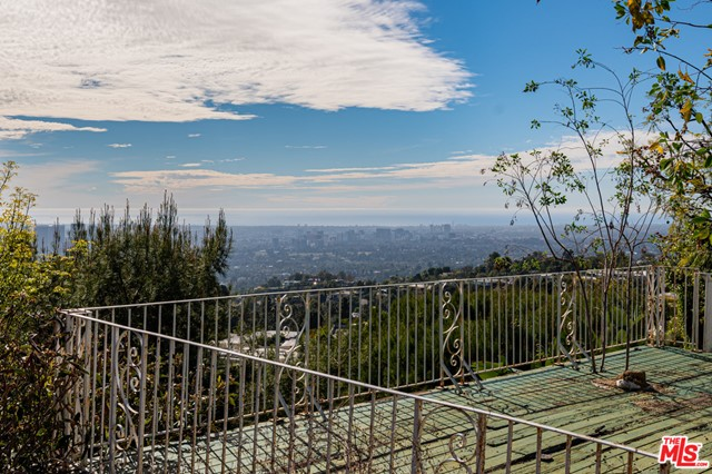 Unique opportunity to acquire a property in prime Trousdale under construction with spectacular views of the LA basin and ocean. The buyer can buy the property and finish it to their own taste. Much of the major construction has been completed while some of the finishes have not been done. The home has extraordinary scale, with a very open floor plan with pocket doors creating the ideal indoor outdoor flow, perfect for entertaining.  There are dramatic sweeping views from the house and pool area. Large flat pad offers generous motor court which can be gated for privacy and security.  The back yard has two large decks over the slope that could not be built today given current codes.